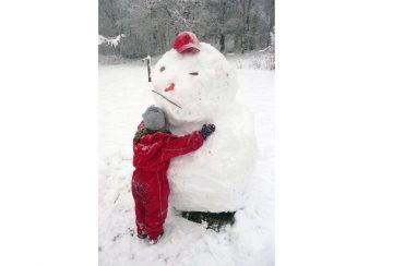 Barn i röd overall kramar en snögubbe med keps