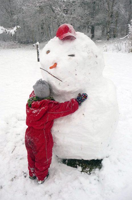 Barn kramar en snögubbe